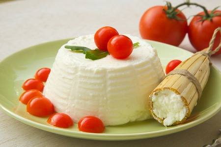ricotta cheese: Ricotta cheese with cherry tomatoes and rucola and a Sicilian traditional mould for making ricotta - cavagne.Close up