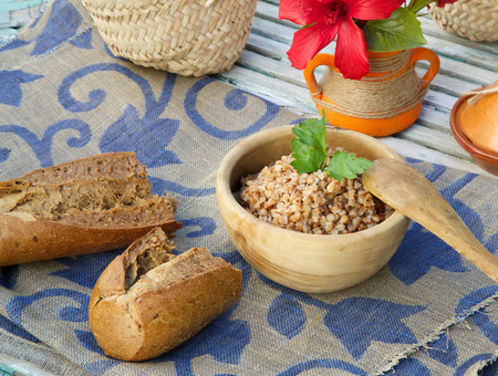 lysine: Healthy lunch: boiled buckwheat cereal in an olive wood plate.Whole grain bread and a flower in the background