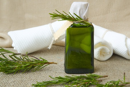 relieving pain: A bottle of rosemary oil. Rosemary twigs in the background. Stock Photo