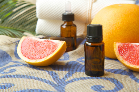 limonene: A dropper bottle of grapefruit essential oil. Grapefruits in the background. Stock Photo