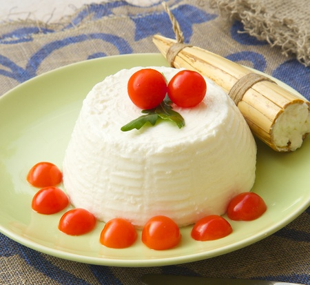 ricotta cheese: Ricotta cheese with cherry tomatoes and rucola and a Sicilian traditional mould for making ricotta - cavagne. Close up