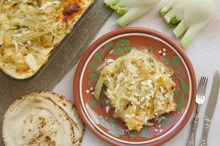 bread mold: Healthy vegetarian dinner: oven baked fennel with potatoes and cheese. Glass mold with a dish , small Lebanese bread, fresh fennel bulbs,fork and a knife. Background. Top view.