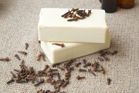 ejaculation: Soap with cloves essential oil. Clove buds in the background. Stock Photo