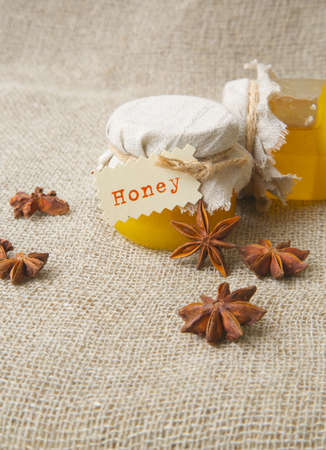 traditional remedy: A glass of honey and star anise fruits on a sackcloth Stock Photo