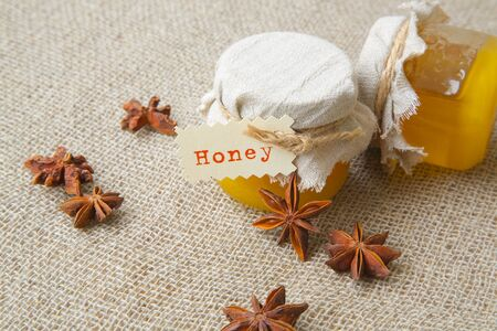home health care: A glass of honey with star anise fruits on a sackcloth