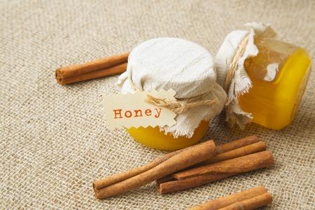 荒布を着たシナモンと蜂蜜のガラス。バック グラウンドでシナモンスティック 写真素材