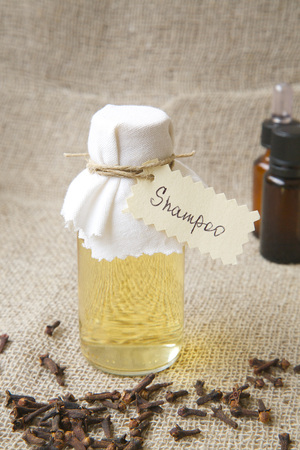 expectorant: Shampoo with clove essential oil. Cloves buds in the background.