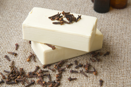 ejaculation: Clove soap on a sackcloth. Cloves buds in the background