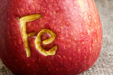colorectal: Abbreviation Fe  scratched on an apple skin. Close up