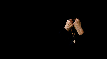 80 years: A senior woman between 70 and 80 years old, dressed in black is praying. Front view
