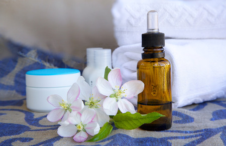 bowels: A dropper bottle of apple blossoms extract and apple blossoms on a sack cloth. Cream box,body lotion,white towels in the background Stock Photo