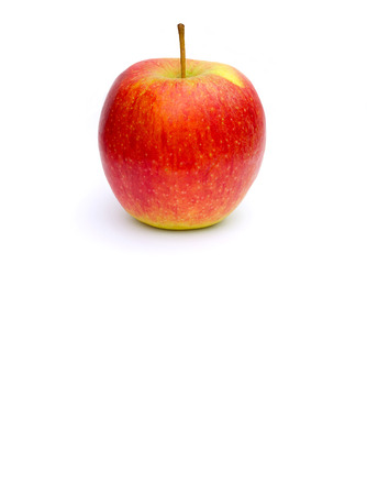 colorectal cancer: A yellow red apple on a white  surface