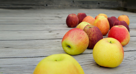 ascorbic acid: Red and pink apples on an old wooden surface Stock Photo