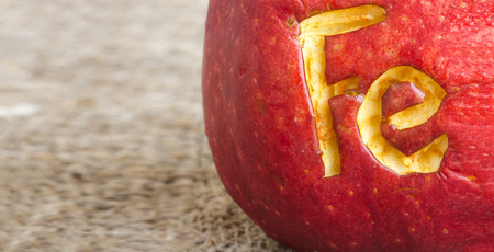 colorectal cancer: Letters  Fe  scratched on an apple skin. Close up.Free space for a text Stock Photo