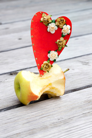 apple core: Apple core and a red heart on an old wooden surface Stock Photo