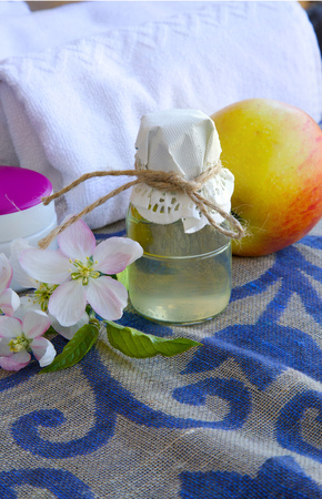 body lotion: A glass bottle of apple blossoms extract and apple blossoms on a sack cloth. Cream box,body lotion,white towels in the background Stock Photo
