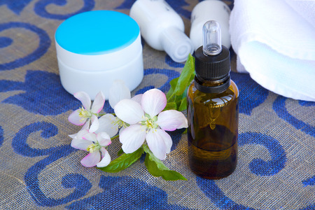 sack cloth: A dropper bottle of apple blossoms extract and apple blossoms on a sack cloth. Cream box,body lotion,white towels in the background Stock Photo
