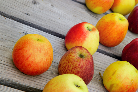 stimulator: Red and pink apples on an old wooden surface Stock Photo