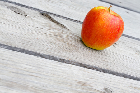 colorectal: A yellow red apple on an old wooden surface