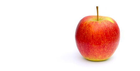 apple gmo: A yellow red apple on a white  surface