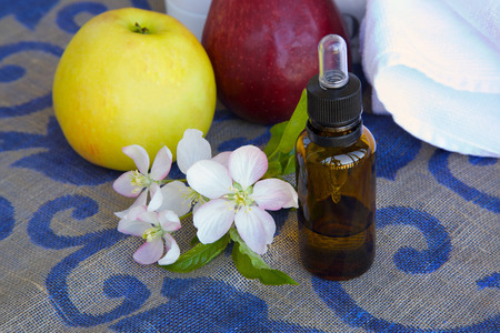 extract: A dropper bottle of apple blossom extract and apple blossoms on a decorative sack cloth