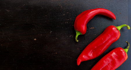 antidiabetic: Fresh red hot chill pepper on a black wooden surface. Background. Free space for a text