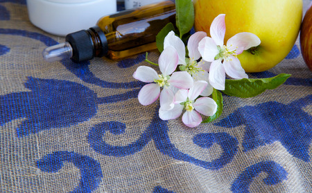 ascorbic acid: Apple blossoms.Apples and dropper bottles in the background.Free space for a text
