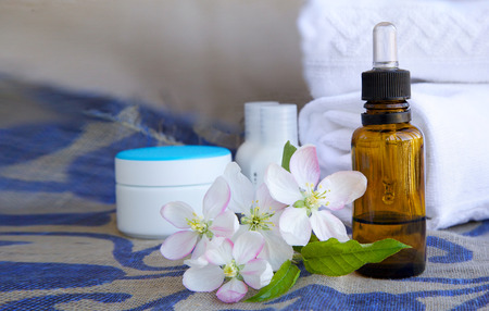 colorectal cancer: A dropper bottle of apple blossoms extract and apple blossoms on a sack cloth. Cream box,body lotion,white towels in the background.Free space for a text