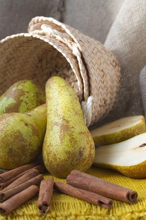 carotenoid: Pears in a woven corbeille and cinnamon sticks