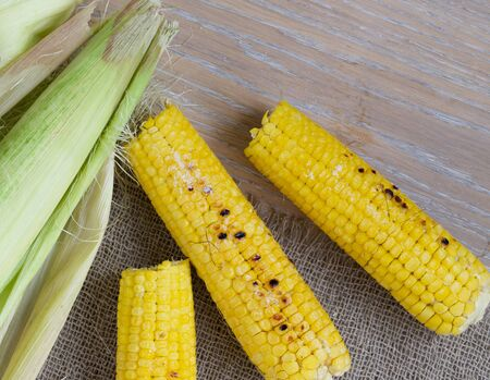 carotenoid: Three grilled corn cobs on a sackcloth.Cloves of garlic.Background