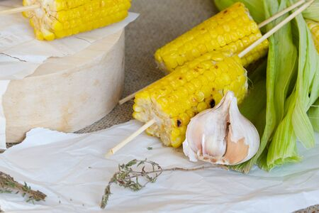 insoluble: Grilled corn skewers prepared with garlic and thyme. It is placed on a piece of paper.Close up
