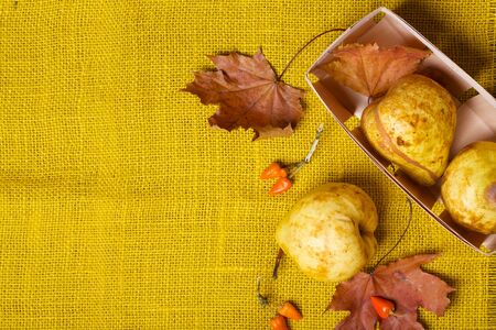 carotenoid: Yellow pears in a wooden basket and cinnamon sticks on a sackcloth