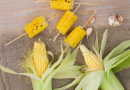 carotenoid: Grilled corn skewers and fresh picked up corn cobs and cloves of garlic on a sackcloth