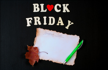 text free space: Black Friday background: shopping list,green plastic pen and a maple leaf on a black wooden chalkboard. Free space for a text.