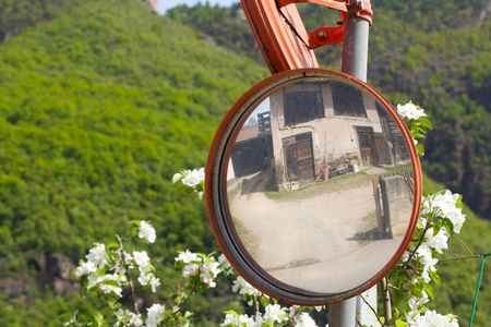 casa antigua: Traffic mirror at complicated countryside street. Old house is reflected in the mirror