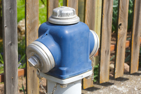 fire hydrant: Pillar-type fire hydrant. Wooden fence in the background