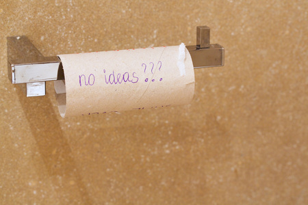 toilet roll: Close-up of finished toilet paper roll in the bathroom where the word -no ideas- are written. Stock Photo