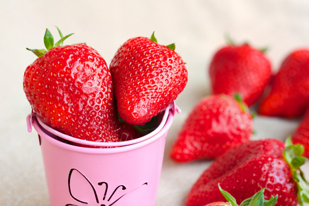 Strawberries in a pink decorative bucket. Fresh strawberries in the background.