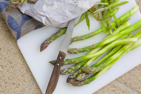 anti ageing: Peeled green asparagus,white plastic cutting board and a knife with a wooden handle