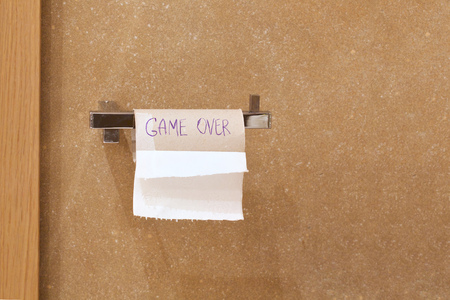 the game is over: Close-up of finished toilet paper roll in the bathroom. Game over is written on the roll.