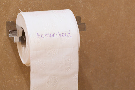 hemorrhoid: The word hemorrhoid is written on a roll of white patterned toilet paper hanging on a holder in a bathroom