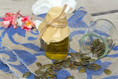 antidiabetic: Pumpkin green seeds oil in a glass bottle on a decorative sackcloth