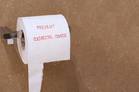 The words prevent colorectal cancer is written on a roll of white patterned toilet paper hanging on a holder in a bathroom.Free space for a text. Stock Photo