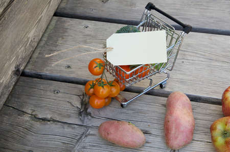 mini farm: Mini shopping cart and fruits with vegetable on a wooden surface.