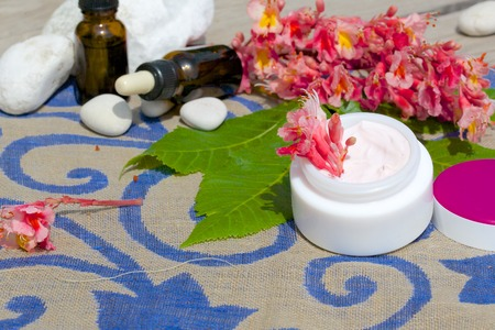 extract: Face cream with chestnut blossoms extract on a decorative sackcloth Stock Photo