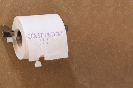 defecation: The word constipation and question mark is written on a roll of white patterned toilet paper hanging on a holder. Free space for a text.
