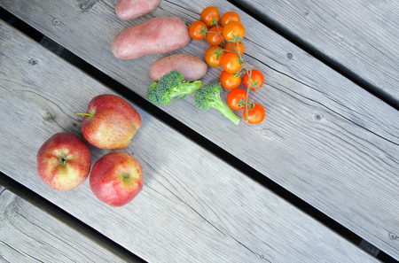 apple gmo: Mini shopping cart and fruits with vegetable on a wooden surface.
