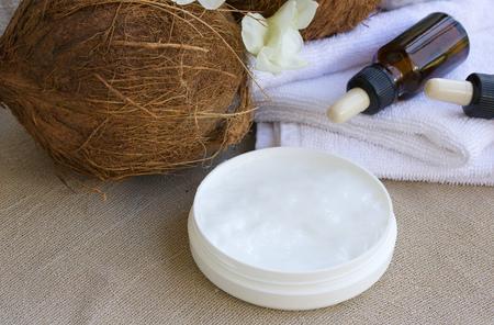 coco: Coco crema corporal mantequilla. Cocos, botellas cuentagotas con aceite de coco, toallas blancas en el fondo.