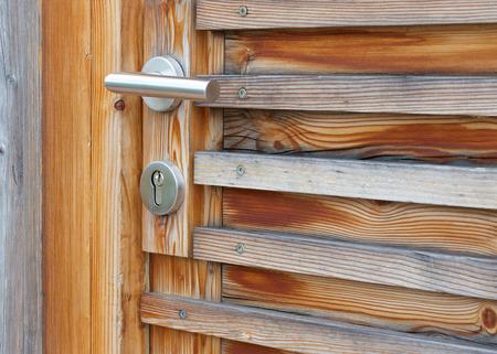 metallic: A metallic doorknob of a wooden door.Closeup