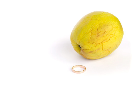colorectal cancer: A marriage ring and an old shrivelled apple isolated over white Stock Photo